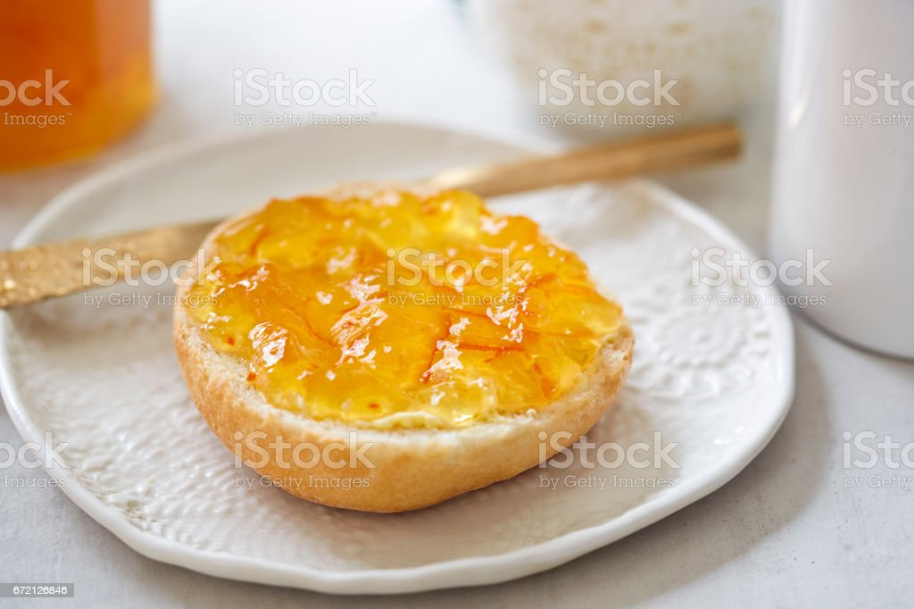 Fresh roll with orange marmalade stock photo