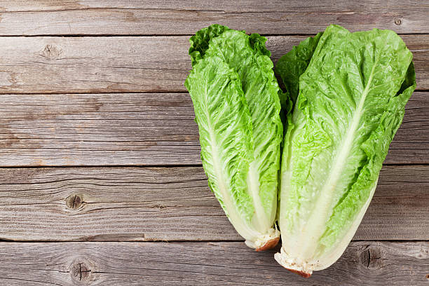 Fresh Romano salad Fresh Romano salad on wooden table. Top view with copy space romaine lettuce stock pictures, royalty-free photos & images