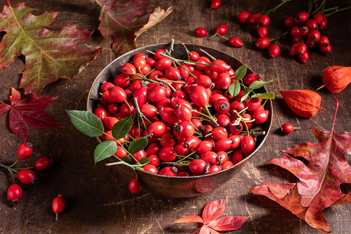 Fresh rose hips in a bowl on a table