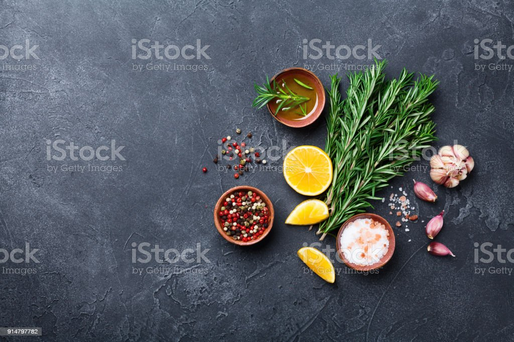 Fresh rosemary and mixed spices on black stone table top view. Ingredients for cooking. Food background. stock photo