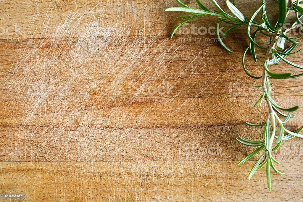 Fresh rosemary on a wood chopping board royalty-free stock photo