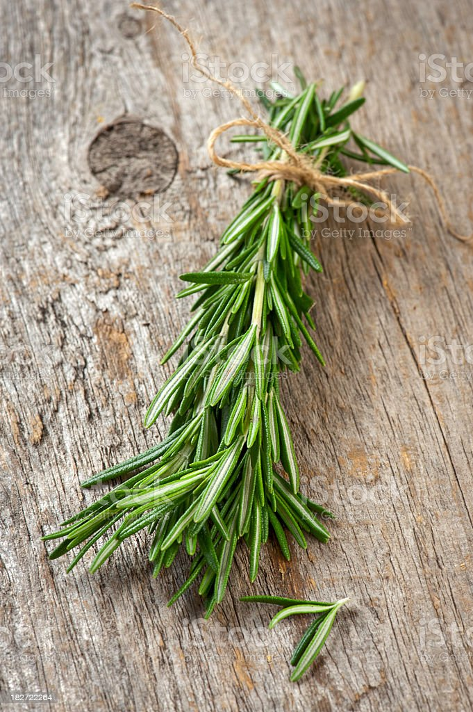 Fresh rosemary tied with a string on a wooden table royalty-free stock photo
