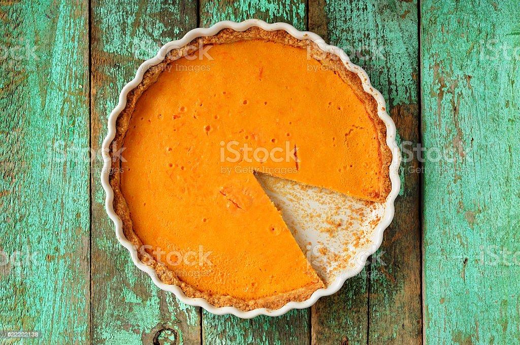 Fresh round bright orange homemade pumpkin pie in white baking stock photo