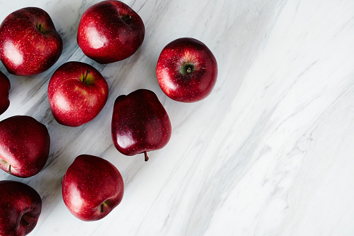 Overhead view of fresh Royal Gala Apples on marble countertop.