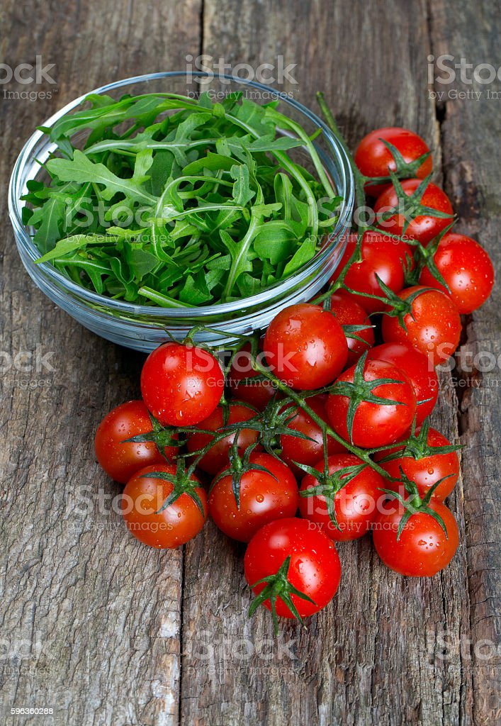 fresh rucola and cherry tomatoes on wooden surface royalty-free stock photo