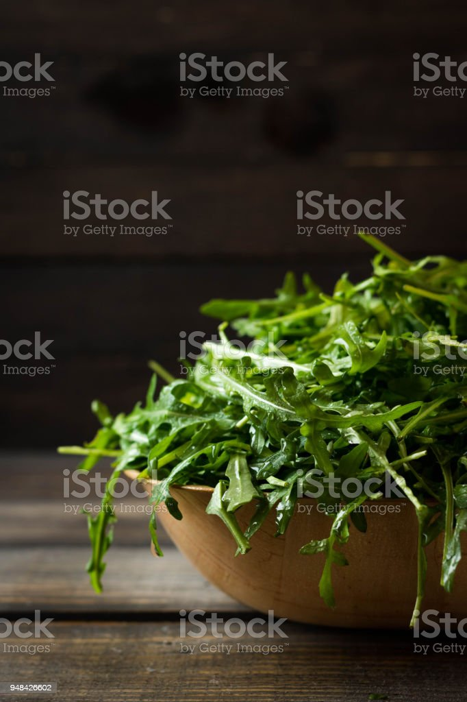 Fresh rucola with water droplets on a dark rustic background stock photo