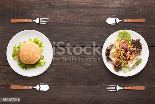 istock Fresh salad and burger on the wooden background. contrasting foo 530427216