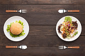 Fresh salad and burger on the wooden background. contrasting food.