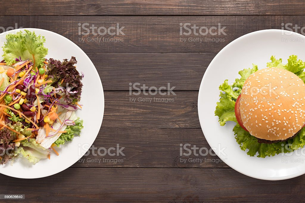 Fresh salad and burger on the wooden background. contrasting food stock photo