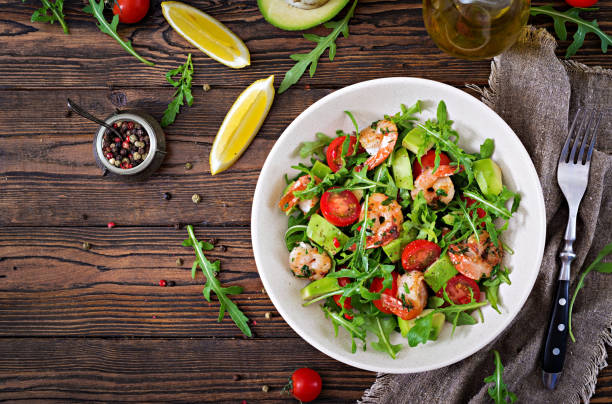 Fresh salad bowl with shrimp, tomato, avocado and arugula on wooden background close up. Healthy food. Clean eating. Top view. Flat lay. stock photo