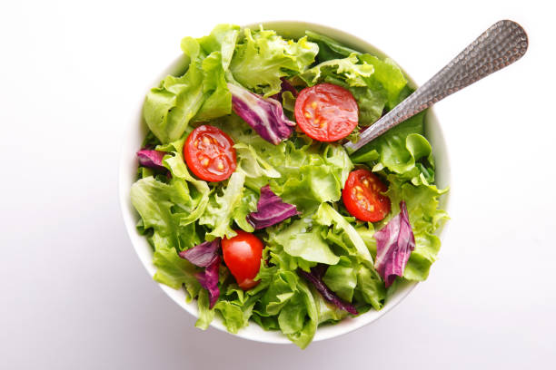 Fresh salad in a bowl. Healthy lettuce and tomato meal on a white background. Top view stock photo