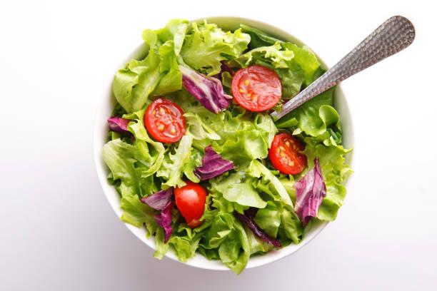 salade fraîche dans un bol. repas sain salade et tomate sur un fond blanc. vue de dessus - saladier photos et images de collection