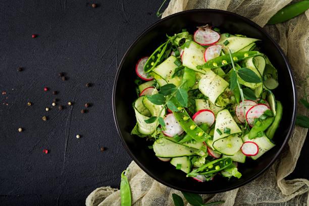frischer salat mit gurken, radieschen, grüne erbsen und kräuter. flach zu legen. ansicht von oben - radieschen salat stock-fotos und bilder