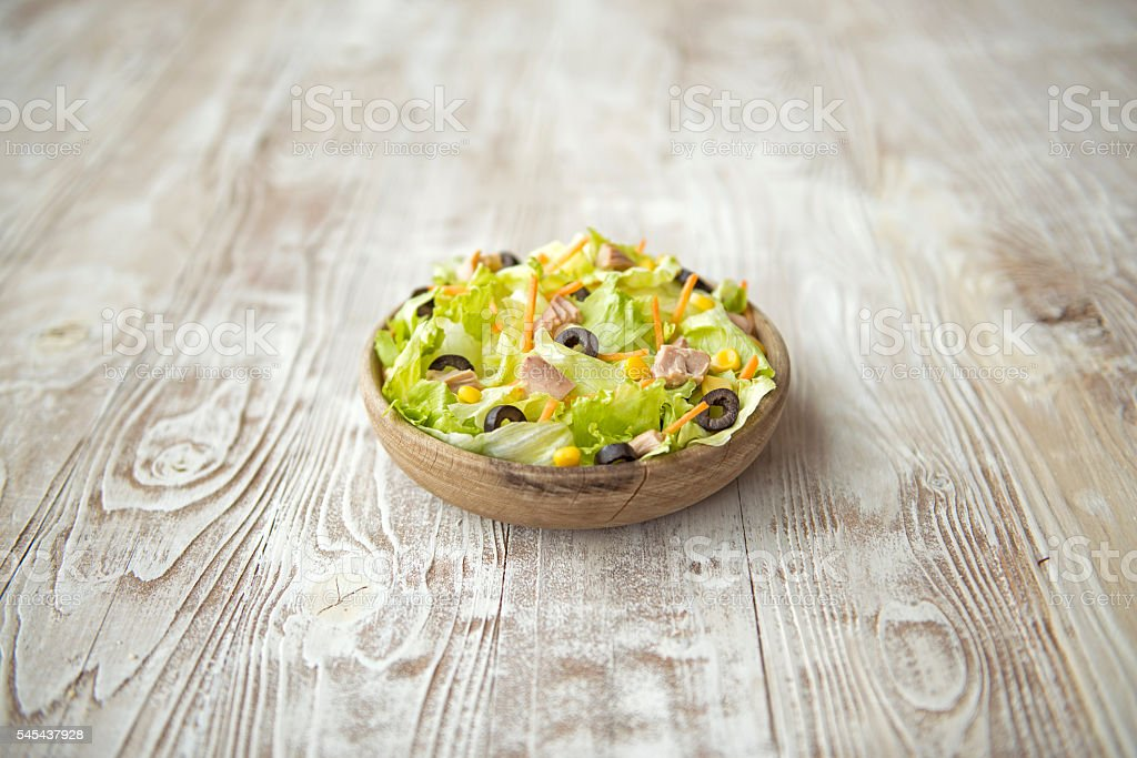 Fresh salad on a wooden table stock photo