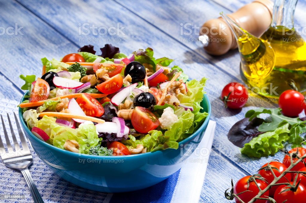 Fresh salad plate on blue picnic table stock photo