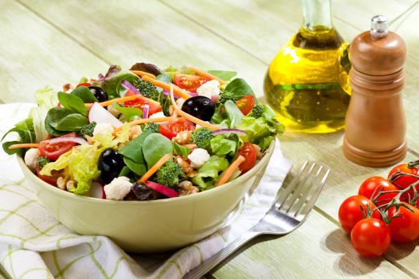 Fresh salad plate on green picnic table stock photo
