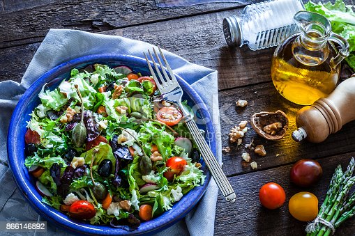 High angle view of a fresh organic salad served in a blue plate shot on rustic wooden table. The plate is at the left side of an horizontal frame on a bluish textile napkin and a salt and pepper shakers as well as an olive oil bottle are at the right placed directly on the wooden table. Predominant colors are green and blue. DSRL studio photo taken with Canon EOS 5D Mk II and Canon EF 100mm f/2.8L Macro IS USM