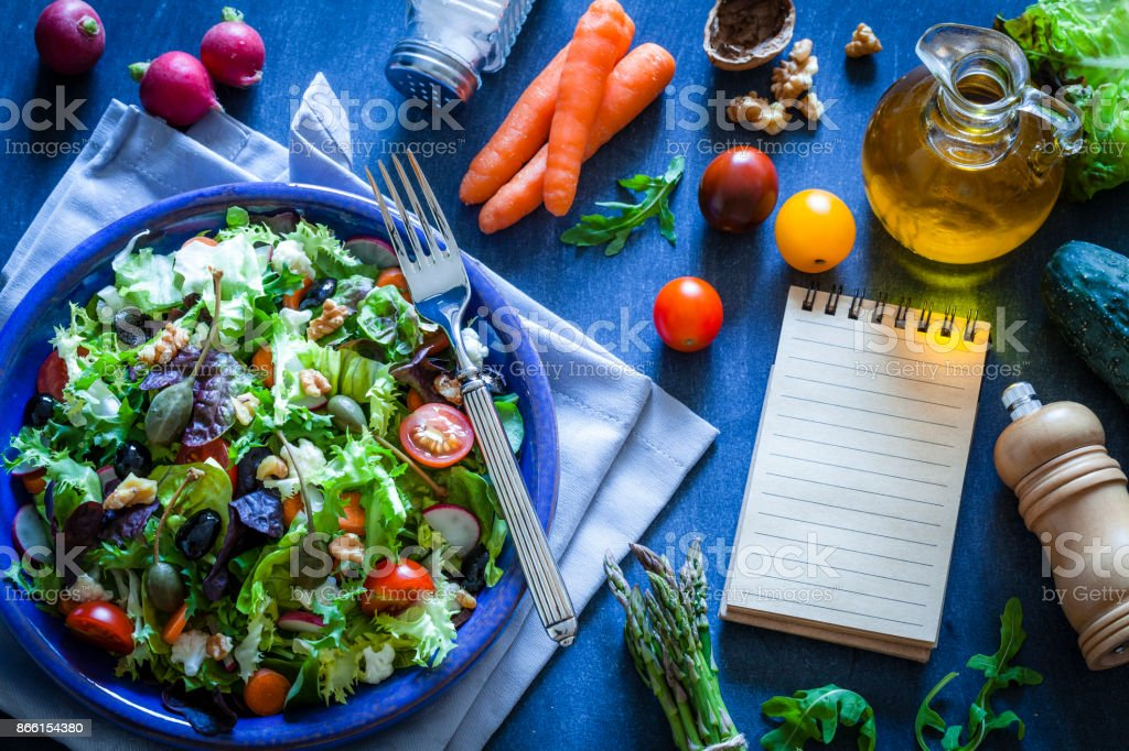 Fresh salad plate with cookbook on bluish kitchen table stock photo