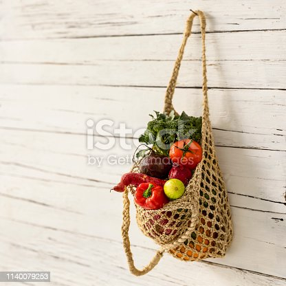 istock Fresh salad vegetables in a natural string reusable bag hanging from an old nail on an old white wooden plank wall. 1140079253