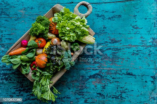 Fresh colorful salad vegetables in an old vintage wooden container bowl on an old distressed weathered turquoise wooden table background, photographed directly above. Vegetables include, broccoli, lettuce, tomato,onion, cucumber, squash, pumpkin, onion, avocado, celery, capsicum, radish, potato, carrot, bok choy and sweetcorn.