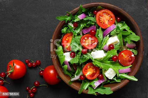 istock Fresh salad with arugula, feta cheese, red onion and red currant in a bowl 836788304