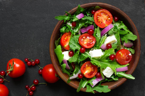 Fresh salad with arugula, feta cheese, red onion and red currant in a bowl stock photo