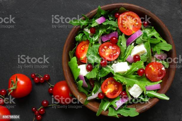 Fresh salad with arugula, feta cheese, red onion and red currant in a bowl on chalkboard background with copy space. top view
