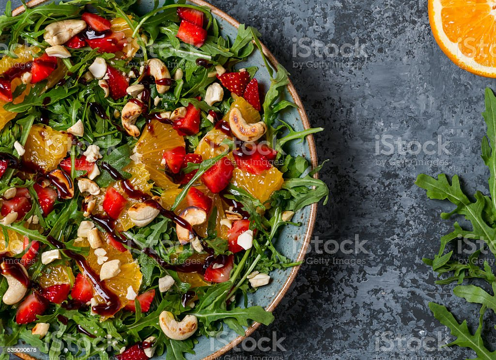 Fresh salad with arugula, fruits and nuts. stock photo