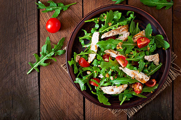 Fresh salad with chicken breast, arugula and tomato stock photo