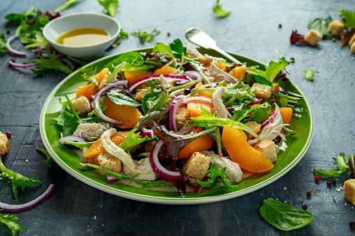 istock Fresh salad with chicken breast, peach, red onion, croutons and vegetables in a green plate. healthy food 943101672