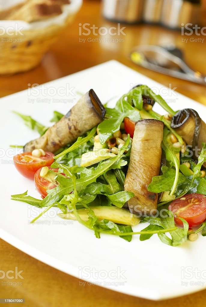 Fresh salad with eggplant, avocado and pine nuts royalty-free stock photo