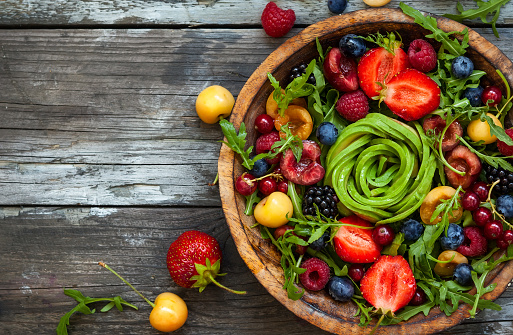 Fresh salad with fruit,berry and vegetables. Healthy food. Top view. Concept of clean food in rustic style.