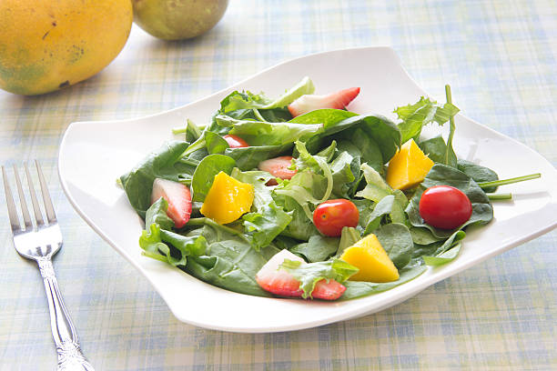Fresh salad with fruits vegetables and greens stock photo