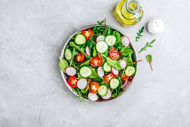 Fresh salad with green leaves of arugula, , spinach, beets, radish, cucumber and tomato on a gray stone background. stock photo