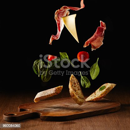 istock Fresh salad with jamon and cheese for sandwich falling on wooden cutting board 992084060
