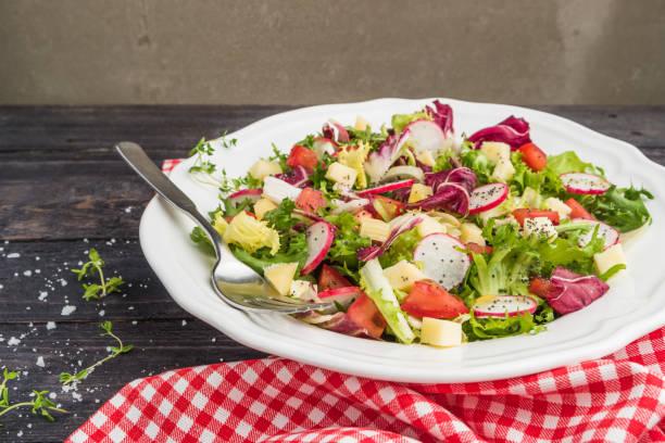 ミックス グリーン、大根、チーズとトマトで木製の背景にあるプレートにサラダ。イタリアの地中海やギリシャ料理。 - ローフード ストックフォトと画像