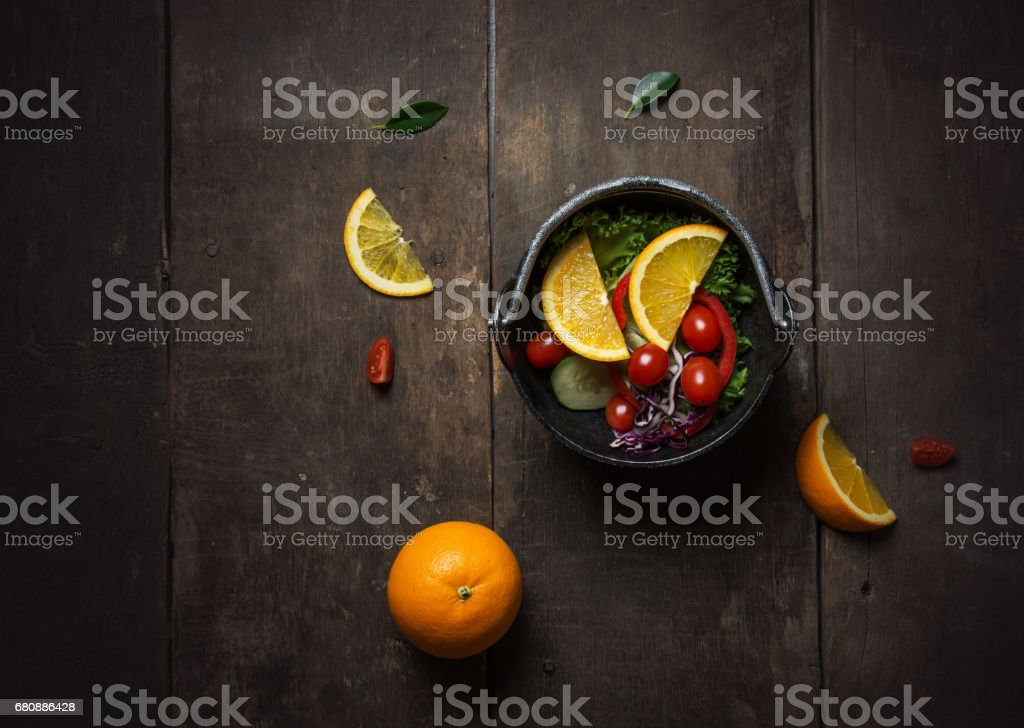 Fresh salad with slice of orange on a wooden background royalty-free stock photo