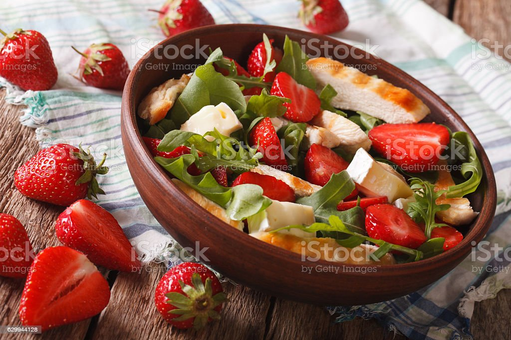 Fresh salad with strawberry, chicken, brie and arugula close-up. stock photo