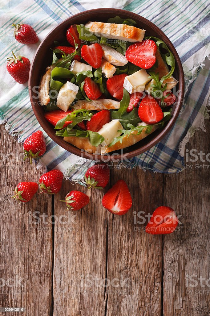Fresh salad with strawberry, chicken, brie and arugula. vertical stock photo