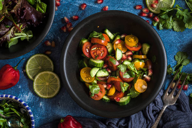 Fresh salad with tomato, cucumber and herbs, flat lay from above Fresh salad with tomato, cucumber and herbs, flat lay from above  The salad is in a black bowl and there are other bowls with ingredients around it. The table is decorated with lime, chili and cilantro. anti inflammatory stock pictures, royalty-free photos & images