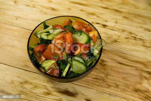 Fresh salad with tomato, cucumber, onion, parsley and dill in glass bowl on wooden table