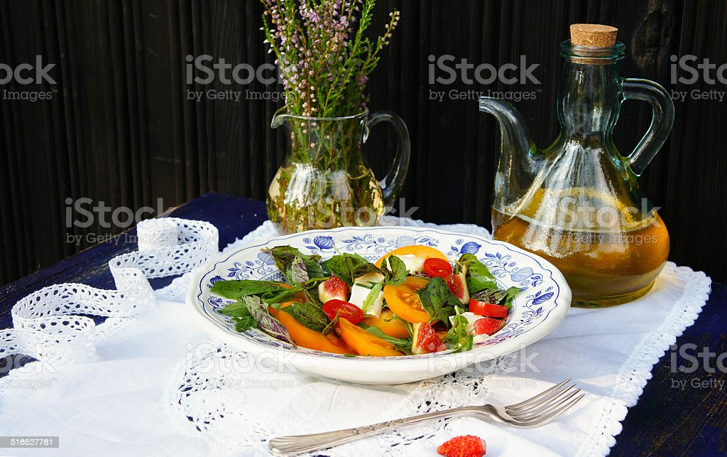 fresh salad with tomatoes, figs, basil and arugula stock photo
