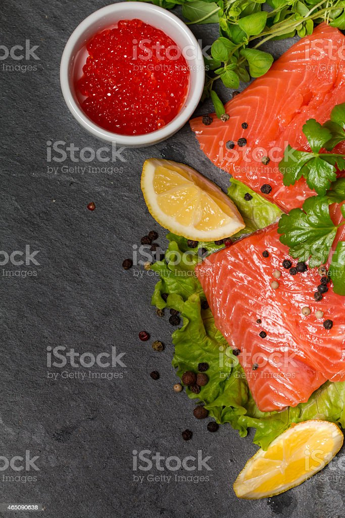 Fresh salmon and red caviar on black plate stock photo