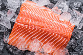 Fresh salmon fillet over ice on black cutting board. Close-up.
