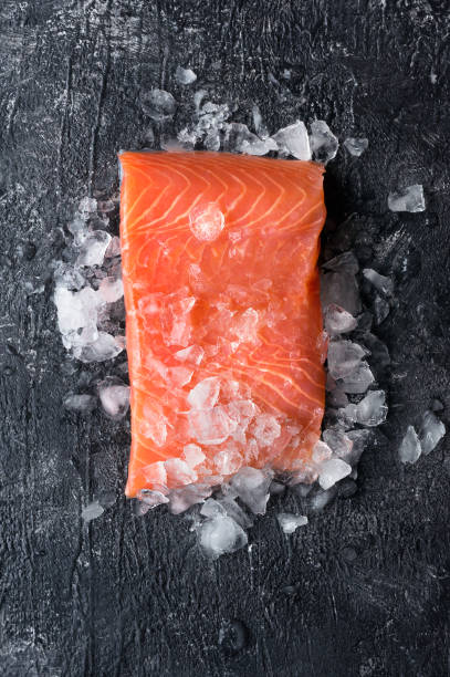 Fresh salmon fillet. Vertical photo. Fresh salmon fillet on ice. Dark slate background. Top view. tuna seafood stock pictures, royalty-free photos & images