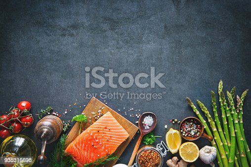istock Fresh salmon fillet with aromatic herbs, spices and vegetables 935316698