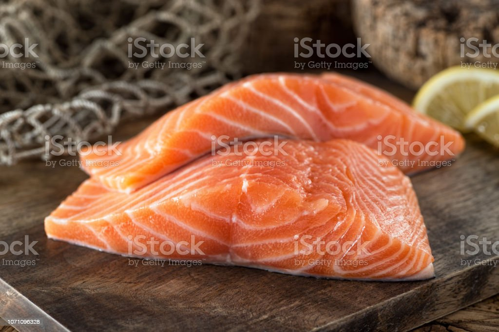 Fresh Salmon Fillets Fresh raw salmon fillets on a wooden board with lemon and fish net background. Acid Stock Photo
