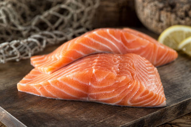 Fresh Salmon Fillets Fresh raw salmon fillets on a wooden board with lemon and fish net background. salmonidae stock pictures, royalty-free photos & images