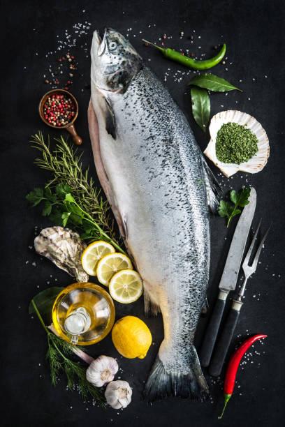 Fresh salmon Fresh salmon fish with seasoning on black stone background atlantic salmon stock pictures, royalty-free photos & images