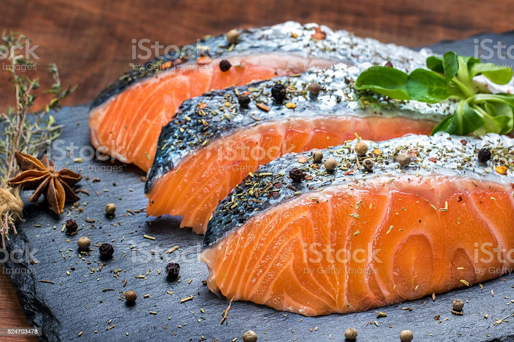 Fresh salmon portions with herb and pepper seasoning. stock photo